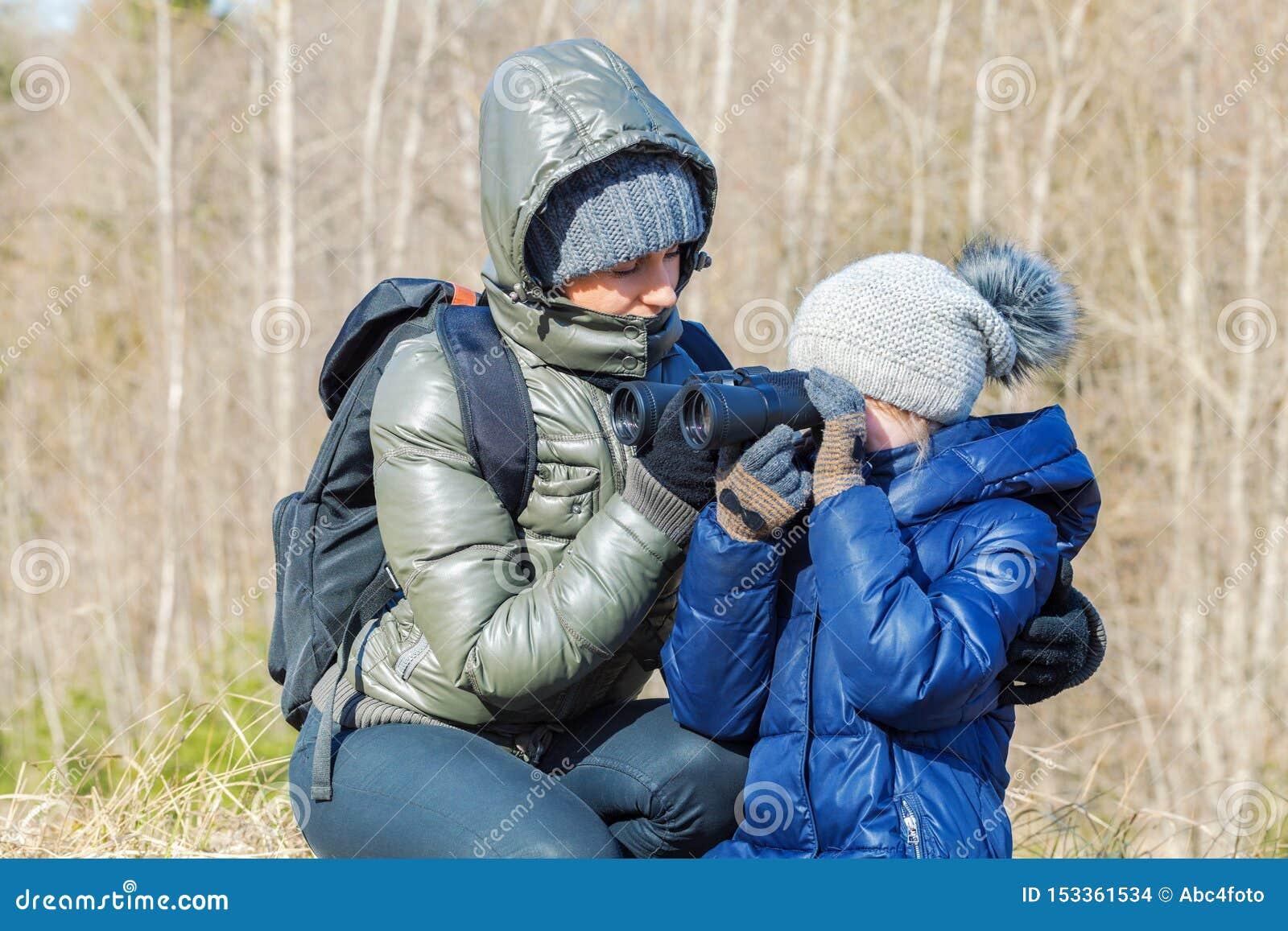Μητέρα και κόρη που χρησιμοποιούν τις διόπτρες σε υπαίθριο στο δάσος