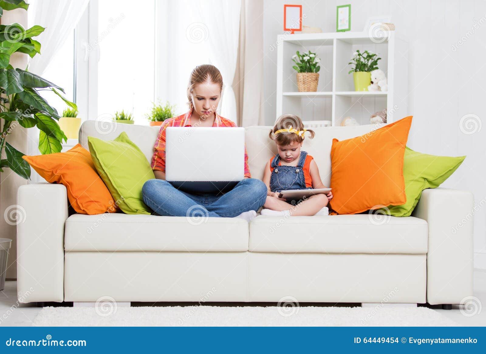 Μητέρα και παιδί με τον υπολογιστή και την ταμπλέτα στο σπίτι, σύμφωνα με
