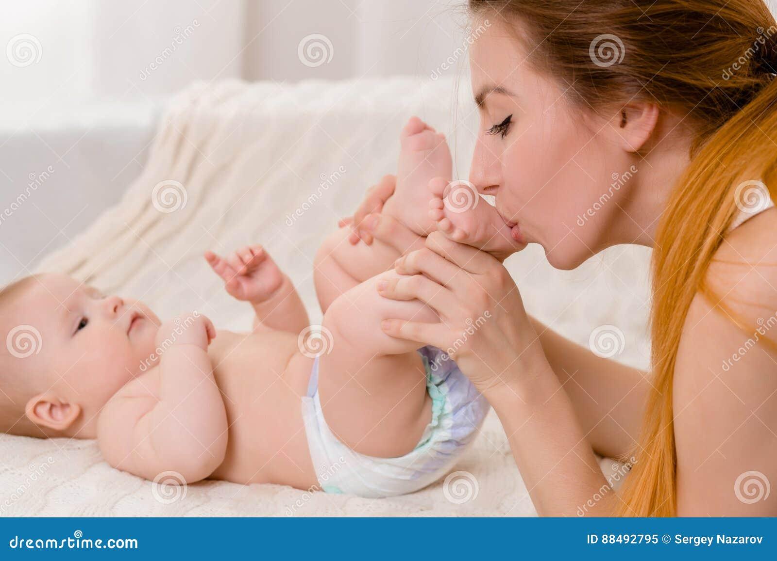 Μητέρα και παιδί σε ένα άσπρο κρεβάτι Mom και κοριτσάκι στο παιχνίδι πανών στην ηλιόλουστη κρεβατοκάμαρα