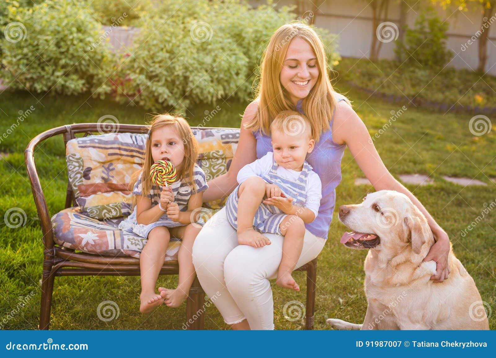 Μητέρα και τα παιδιά της που χαλαρώνουν στον κήπο με το σκυλί της Pet Ευτυχές οικογενειακό παιχνίδι με retriever του Λαμπραντόρ τ