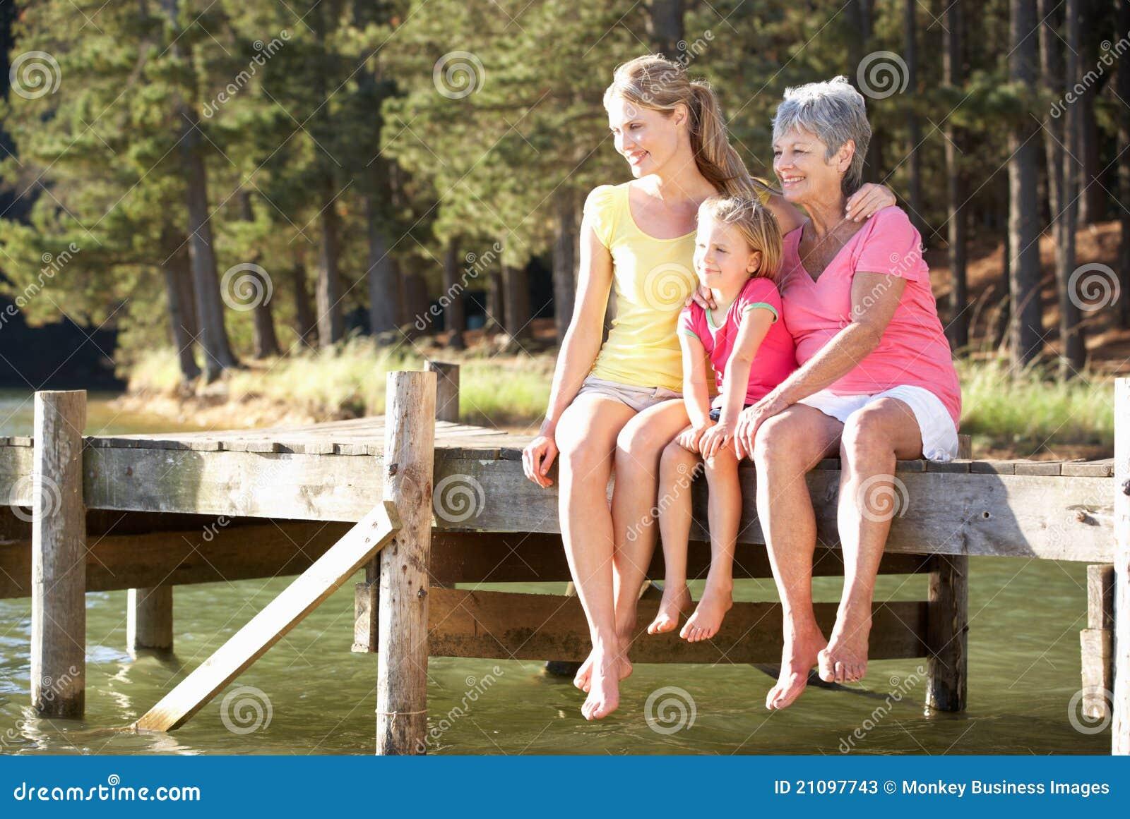Μητέρα, κόρη και γιαγιά που κάθονται από τη λίμνη