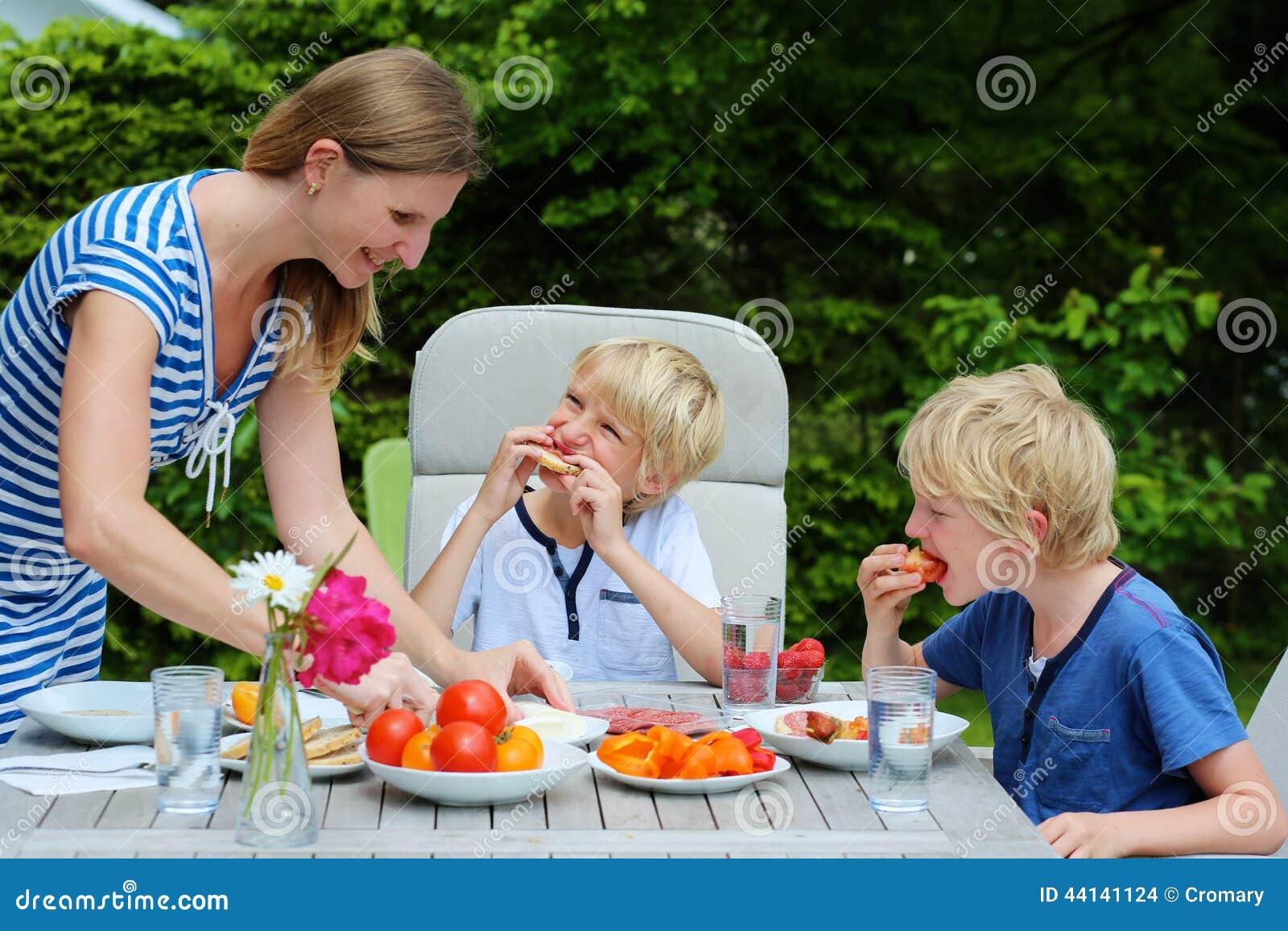 Μητέρα με τα παιδιά που τρώνε υπαίθρια