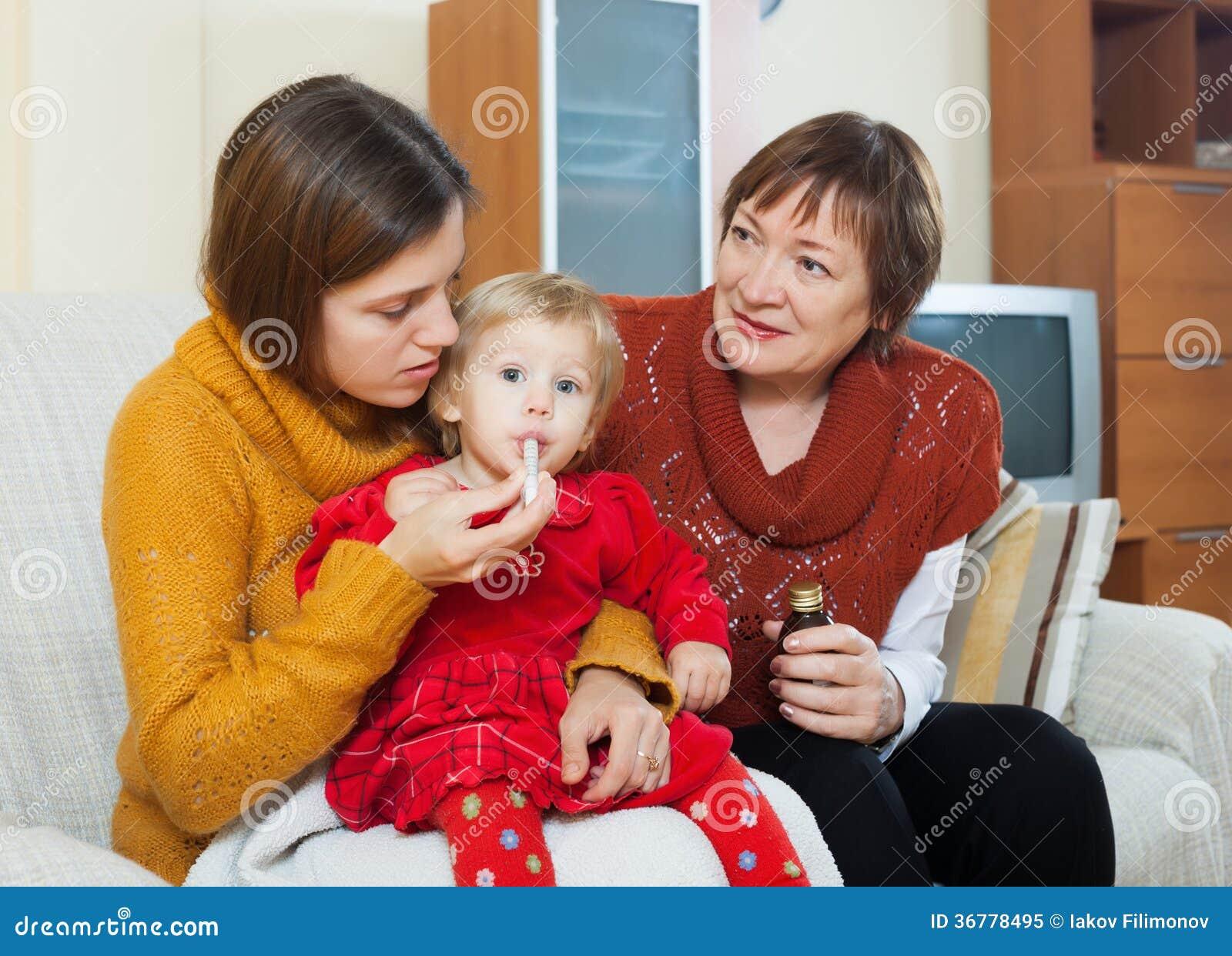 Μητέρα με την ώριμη φροντίδα γιαγιάδων για το άρρωστο μικρό παιδί