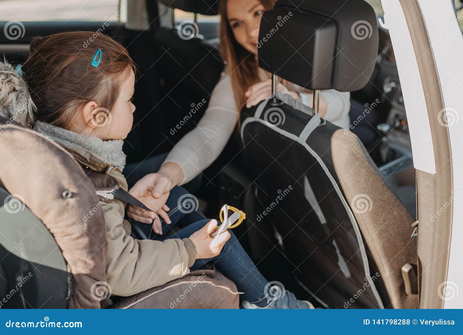 Μητέρα που εξασφαλίζει την κόρη μικρών παιδιών της που κουμπώνεται στο κάθισμα αυτοκινήτων μωρών της
