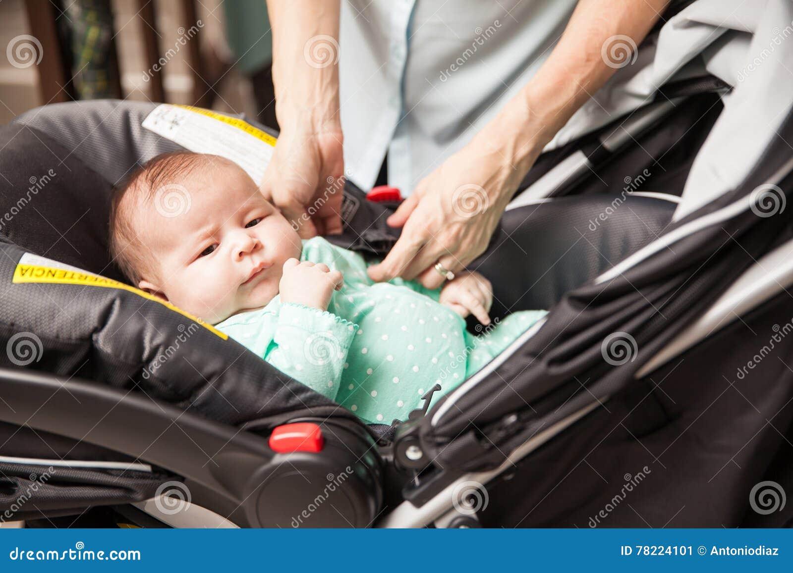 Μητέρα που εξασφαλίζει το μωρό στο μεταφορέα