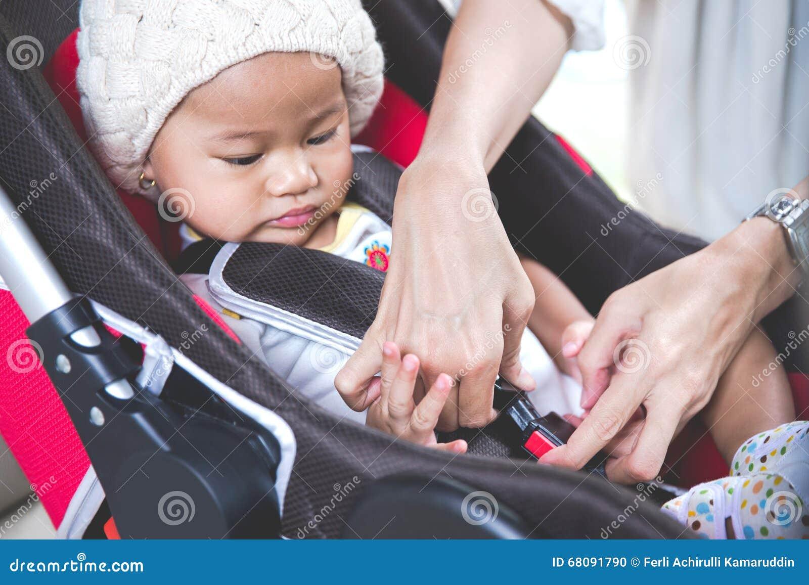 Μητέρα που εξασφαλίζει το μωρό της στο κάθισμα αυτοκινήτων στο αυτοκίνητό της