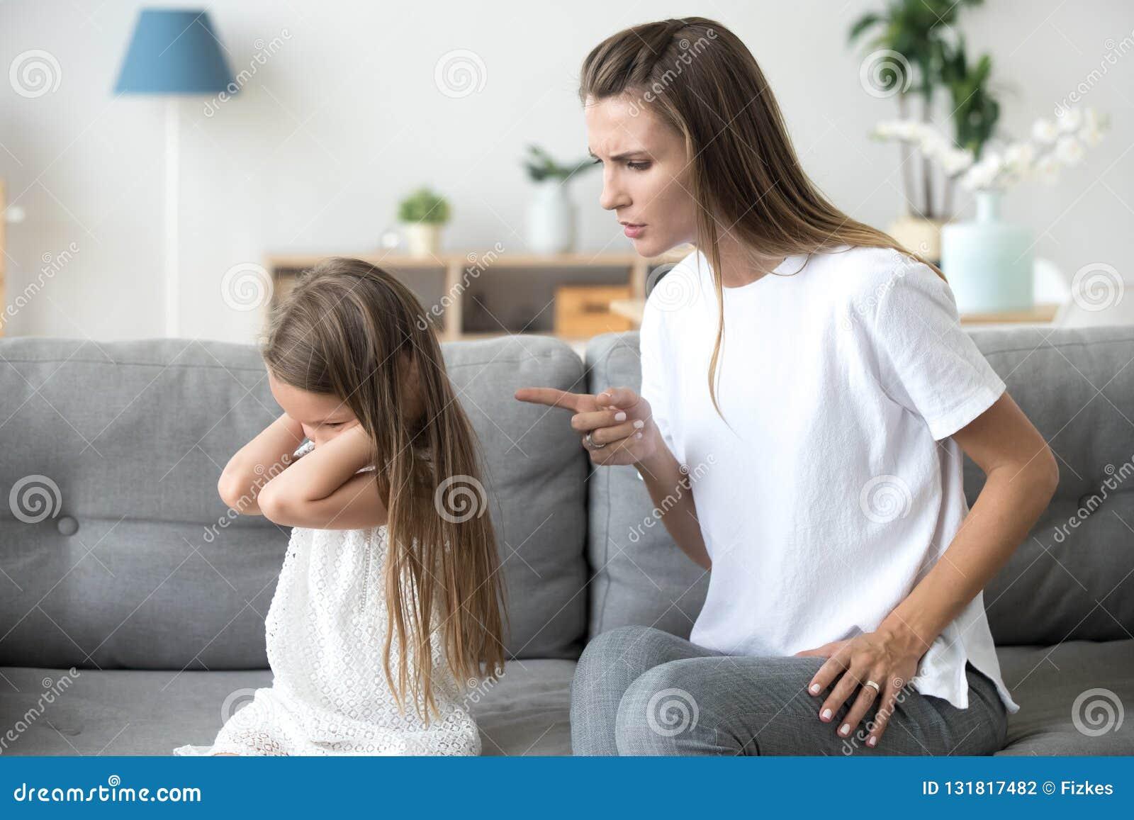μητέρα που επιπλήττει τα επίμονα κλείνοντας αυτιάη παιδιών που δεν ακούνε