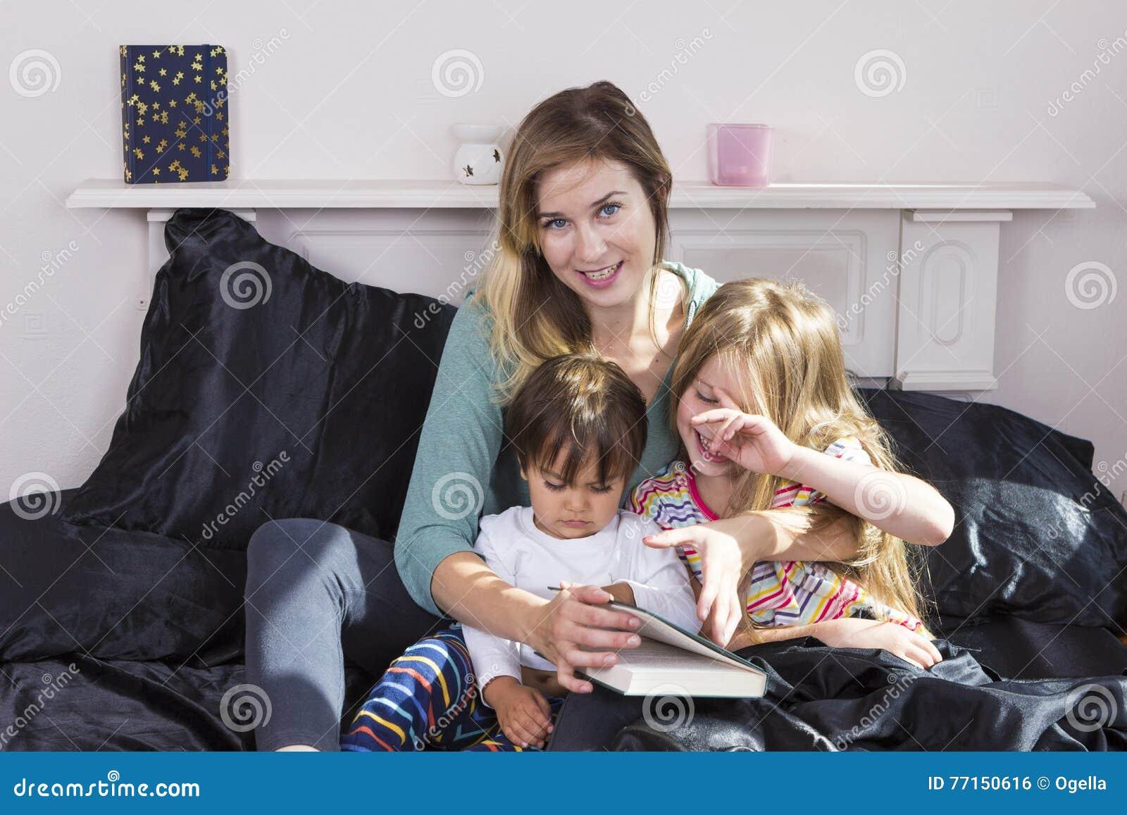 Μητέρα που διαβάζει στα παιδιά στο κρεβάτι