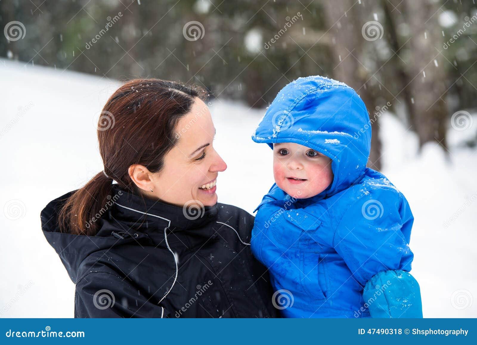 Μητέρα που χαμογελά στο γιο μωρών έξω το χειμώνα