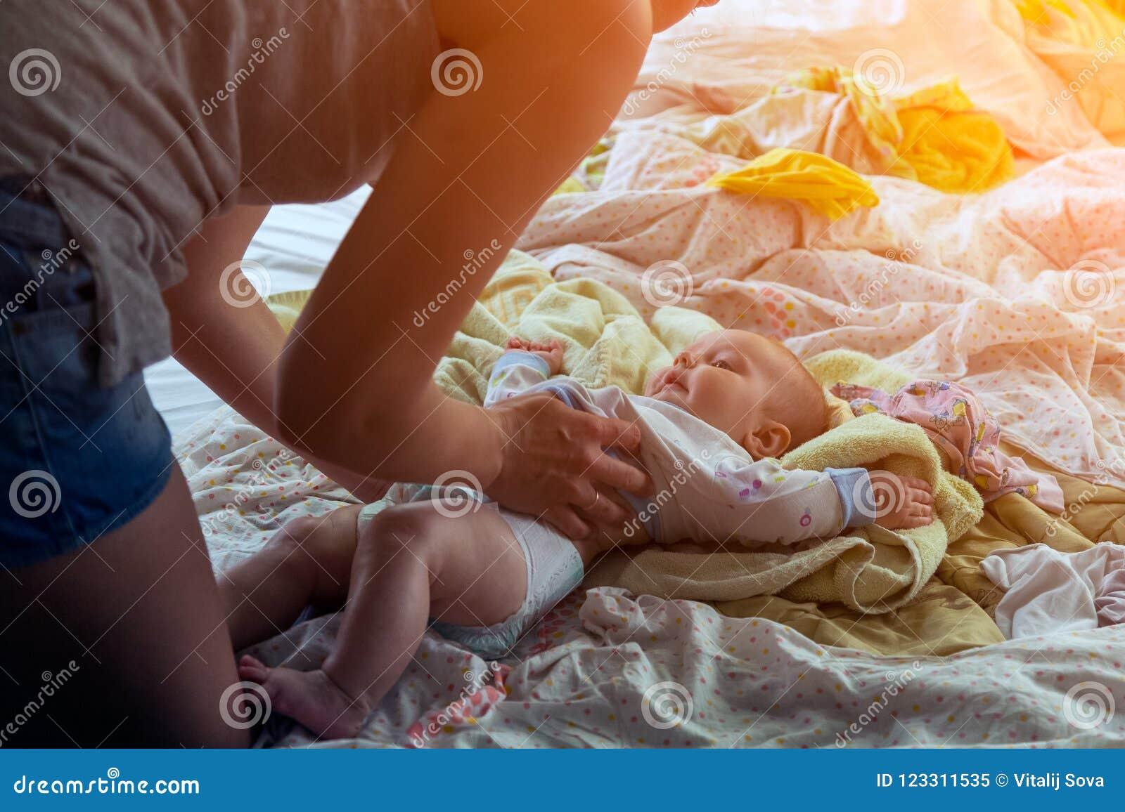 Μητέρα swaddles και φορέματα ένα μικρό κοριτσάκι