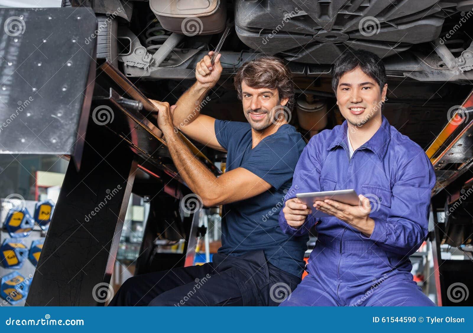 Μηχανικοί με την ψηφιακή ταμπλέτα που λειτουργεί κάτω από ανυψωμένος