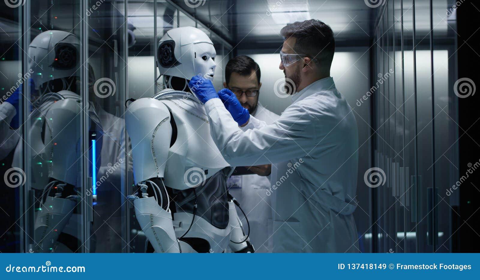 Μηχανικοί που εξετάζουν στους ελέγχους ρομπότ μέσα στο εργαστήριο