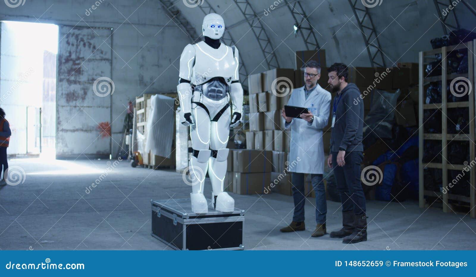 Μηχανικοί που εξετάζουν το ρομπότ σε μια αποθήκη εμπορευμάτων