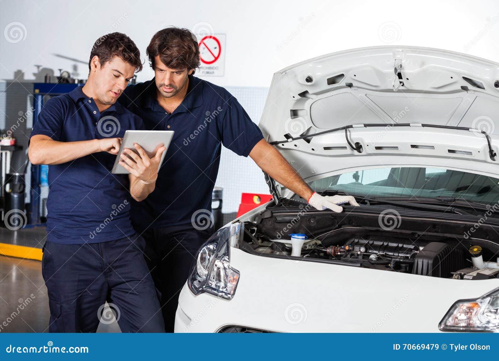 Μηχανικοί που χρησιμοποιούν τον υπολογιστή ταμπλετών με το χαλασμένο αυτοκίνητο
