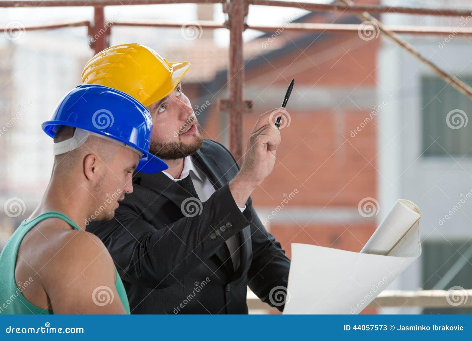 Μηχανικός και εργάτης οικοδομών που συζητούν ένα πρόγραμμα