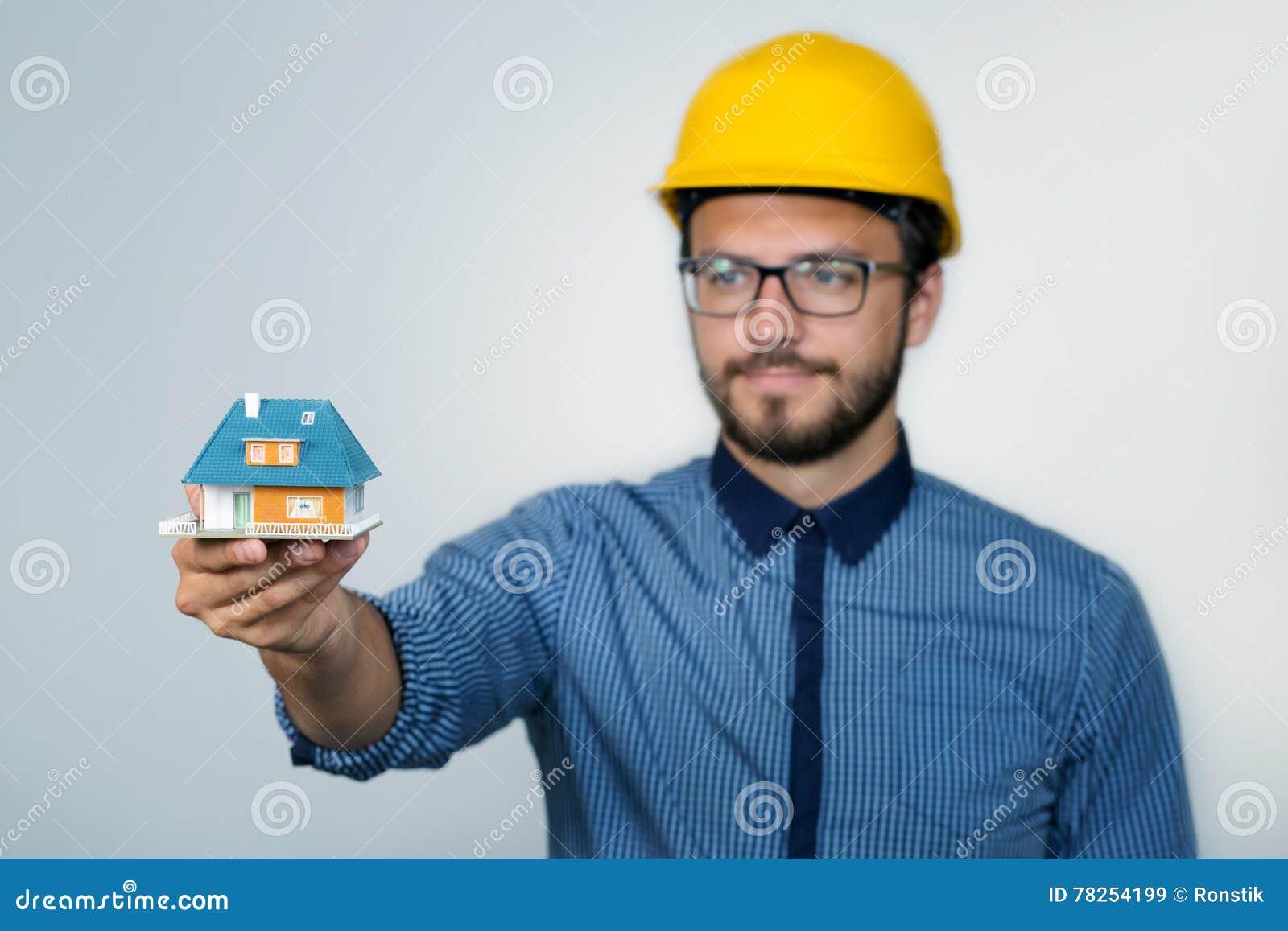 Μηχανικός κατασκευής που παρουσιάζει μικρό πρότυπο σπιτιών