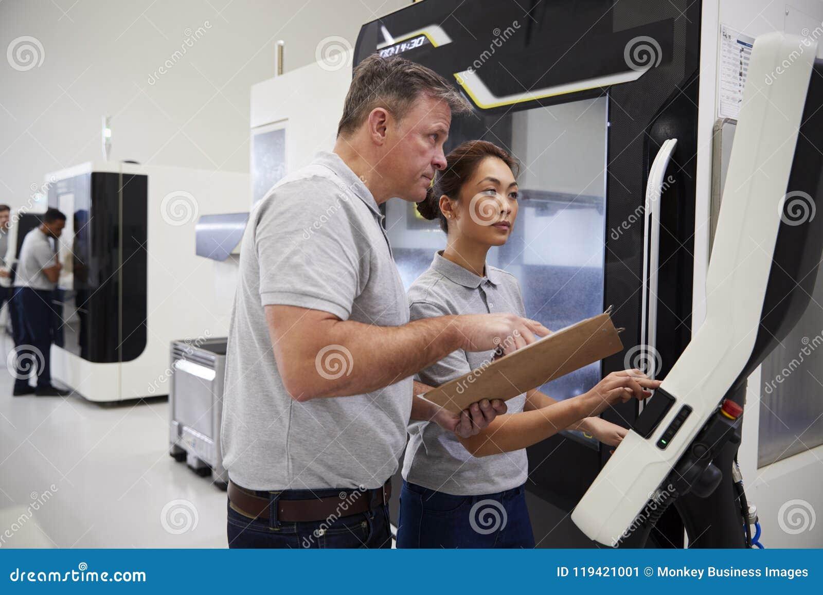 Μηχανικός που εκπαιδεύει το θηλυκό μαθητευόμενο για να χρησιμοποιήσει CNC τη μηχανή στον παράγοντα
