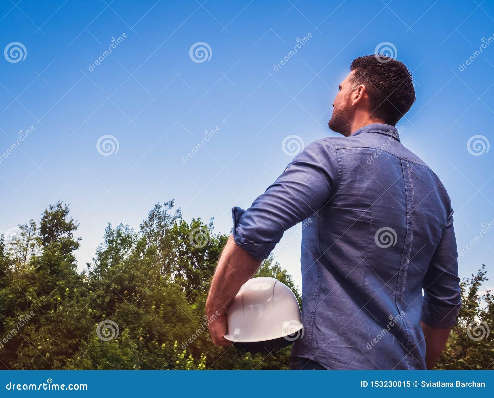 Μηχανικός, που κρατά άσπρο hardhat στο πάρκο