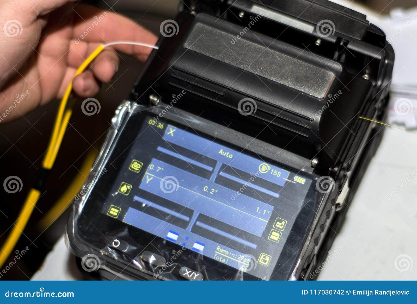 Μηχανικός που συνδέει το καλώδιο οπτικών ινών με Splicer τήξης οπτικής ίνας με το εργαλείο με την επίδειξη