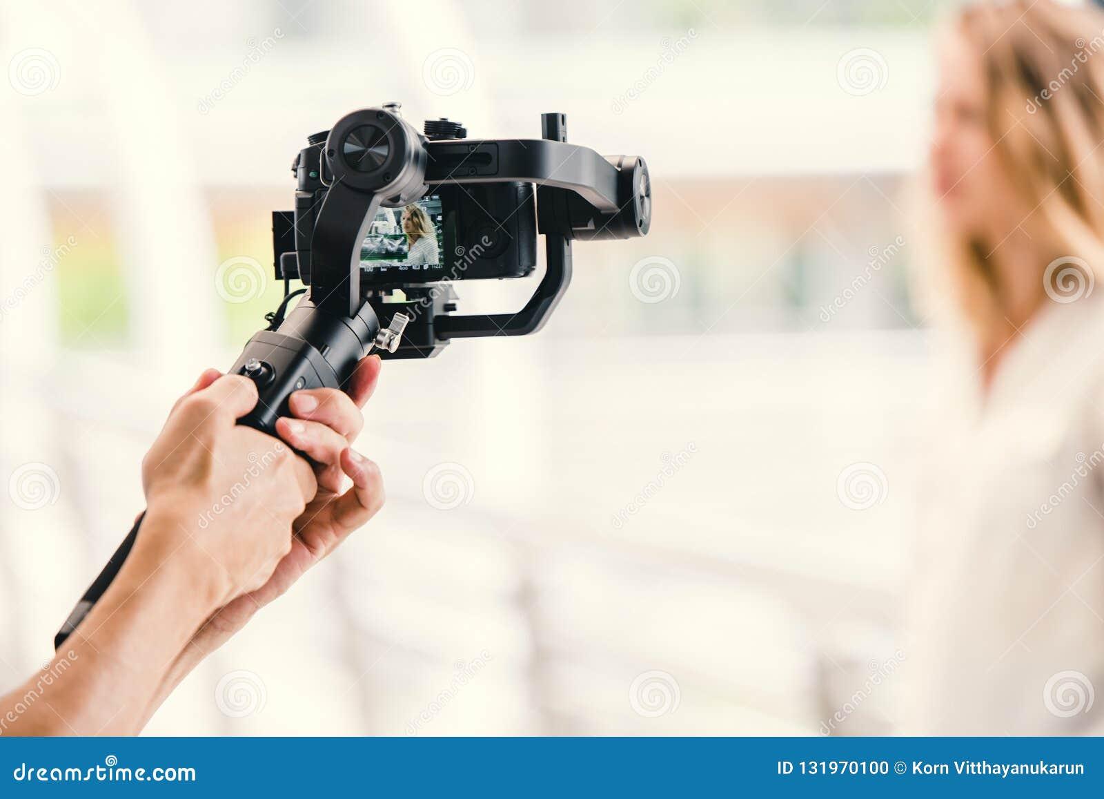 Μηχανοποιημένος αναρτήρας, videographer χρησιμοποιώντας dslr το αντι εργαλείο κουνημάτων καμερών για το σταθεροποιητή