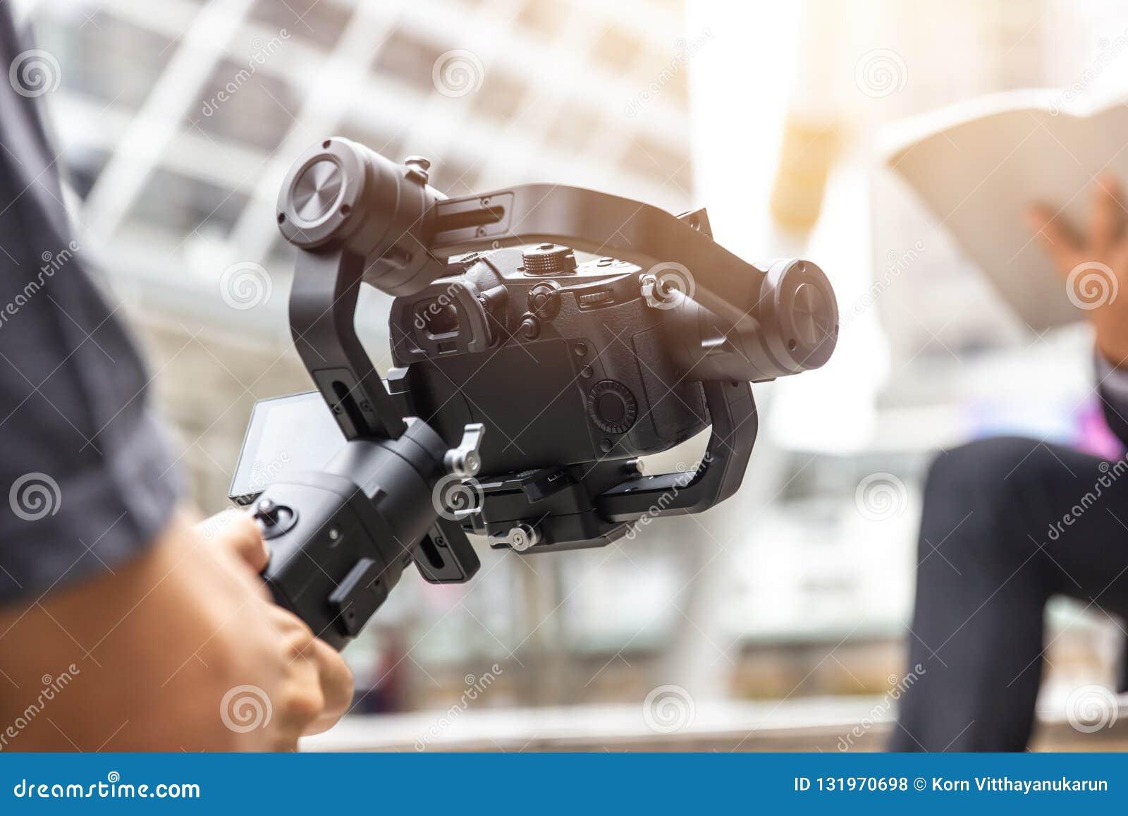 Μηχανοποιημένος αναρτήρας, videographer χρησιμοποιώντας dslr το αντι εργαλείο κουνημάτων καμερών