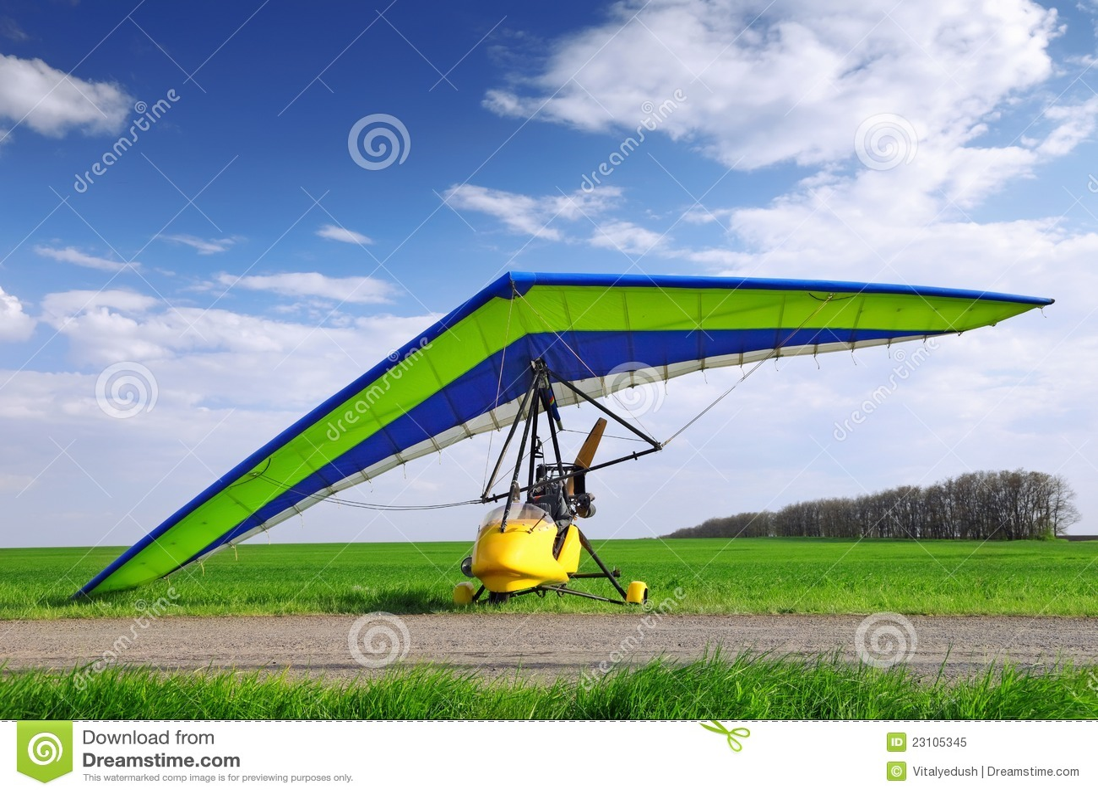 Μηχανοποιημένος κρεμάστε το ανεμοπλάνο πέρα από την πράσινη χλόη