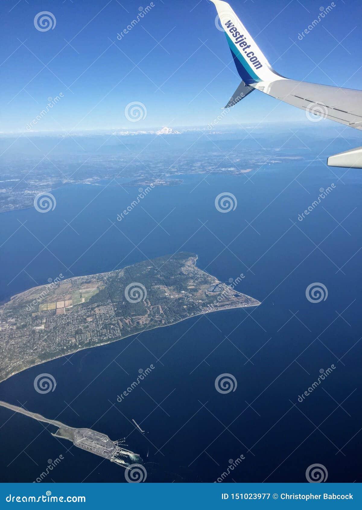 Μια άποψη από το παράθυρο επιβατών ενός φτερού ενός αεροπλάνου Westjet που πετά επάνω από τον ωκεανό μακριά Βικτώριας, Βρετανική