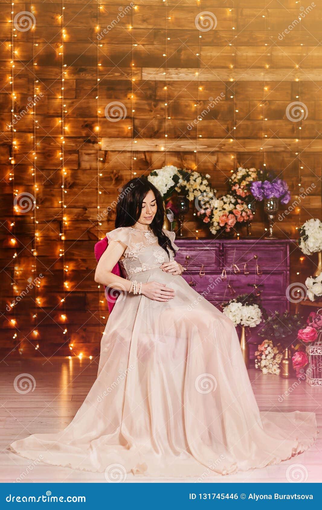 Μια έγκυος γυναίκα σε μια όμορφη μακριά εσθήτα στο στούντιο
