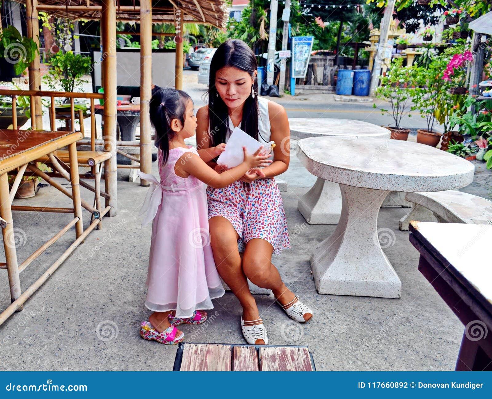 Μια αγαπώντας κόρη παρουσιάζει στη μητέρα της με μια κάρτα γενεθλίων σε ένα υπαίθριο εστιατόριο στην Ταϊλάνδη