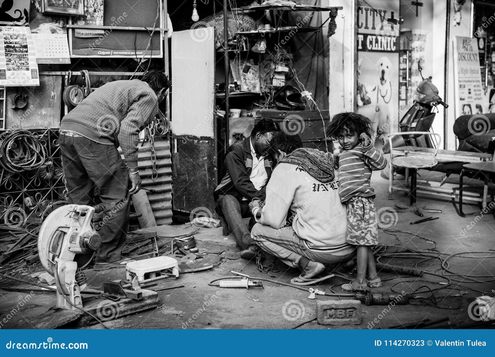 Μια γραπτή εικόνα με ένα ινδικό αγόρι που παίζει γύρω από τον μπαμπά του ενώ ο πατέρας εργάζεται