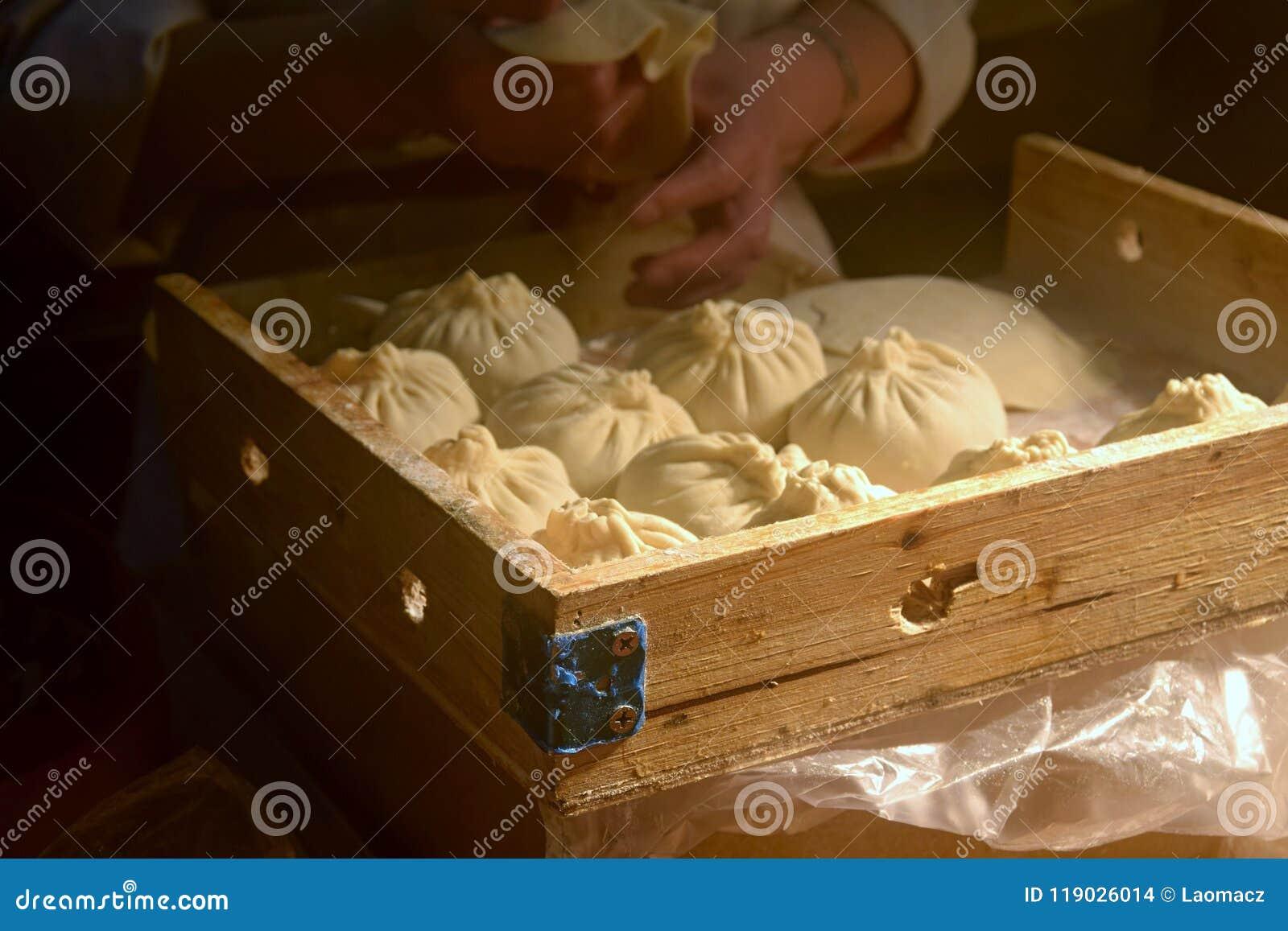 Μια γυναίκα κάνει τη ζύμη το κινεζικό bao zi ` μπουλεττών ` που γεμίζεται με το κρέας και το λαχανικό