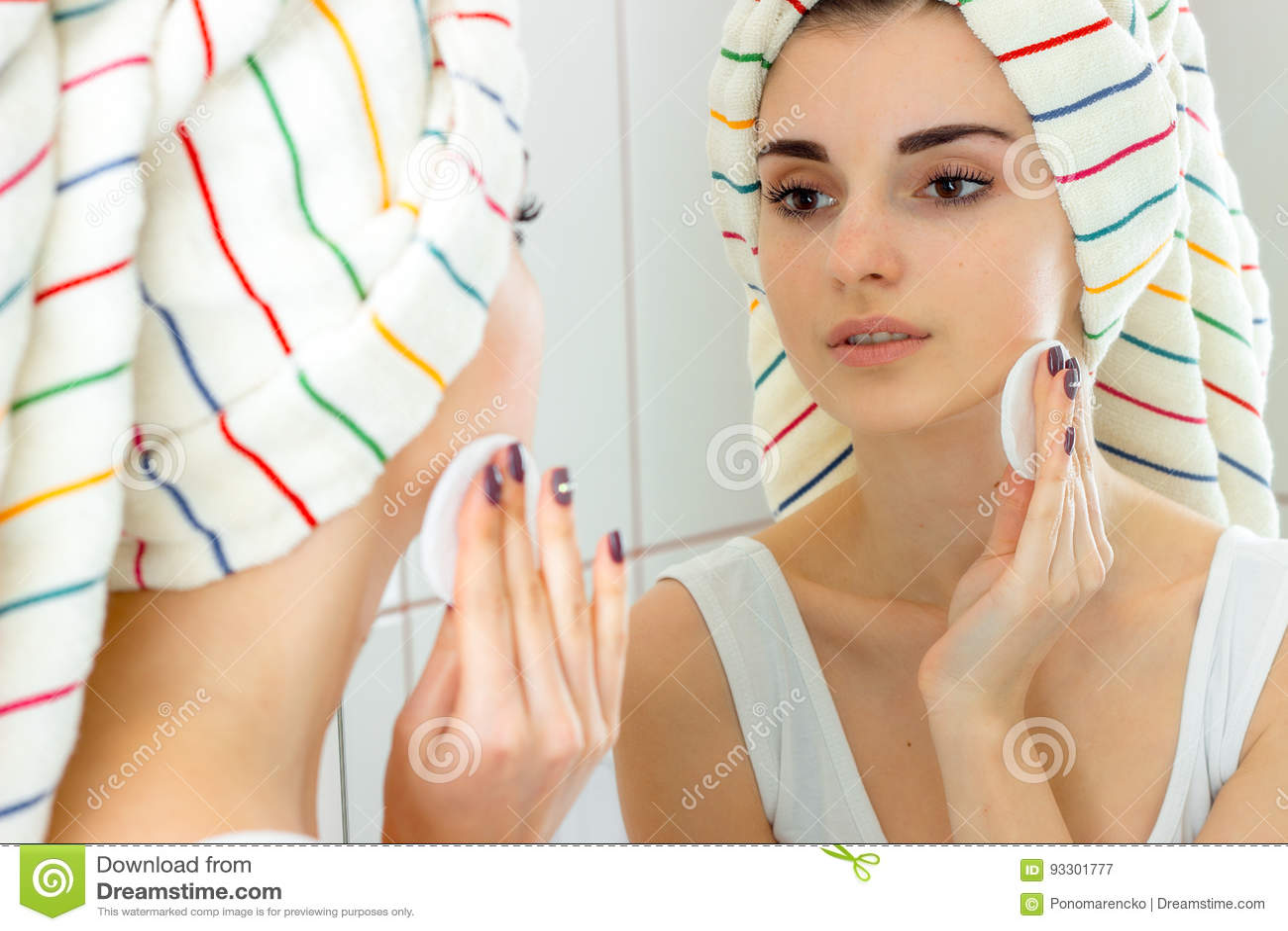 Μια γυναίκα με μια πετσέτα στο κεφάλι της καθαρίζει το του προσώπου makeover