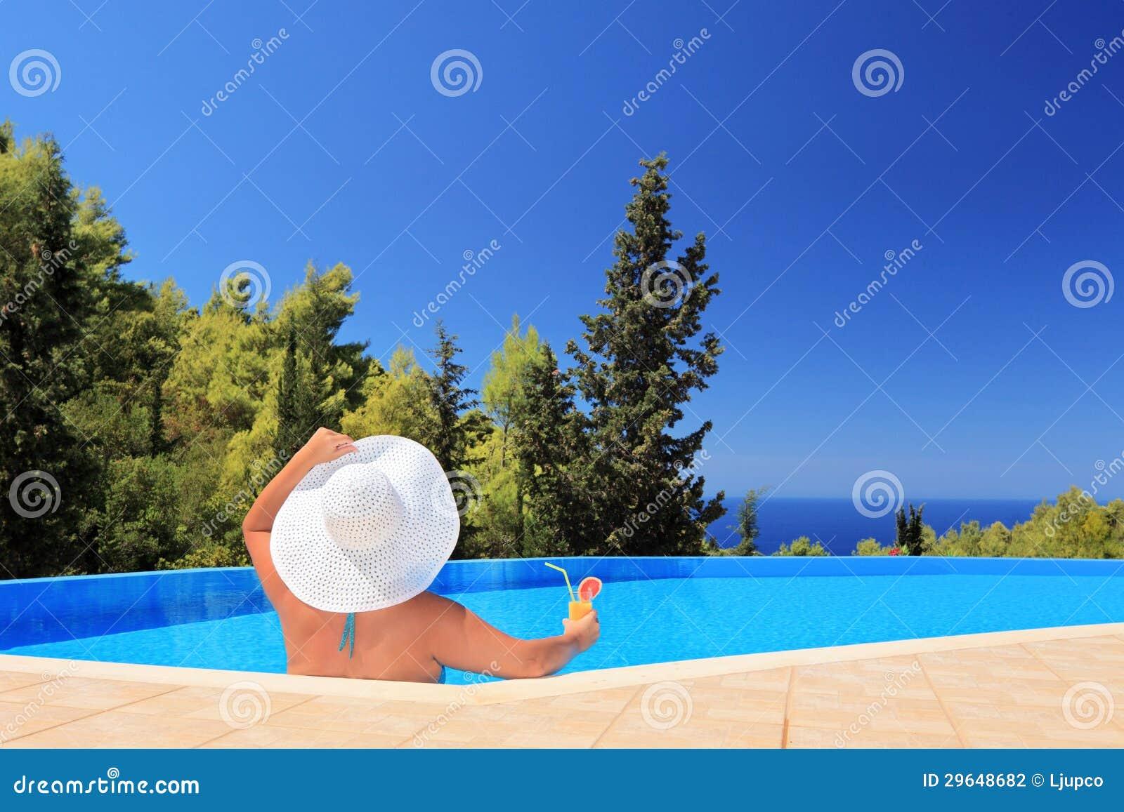Μια γυναίκα που χαλαρώνει σε μια πισίνα με το κοκτέιλ