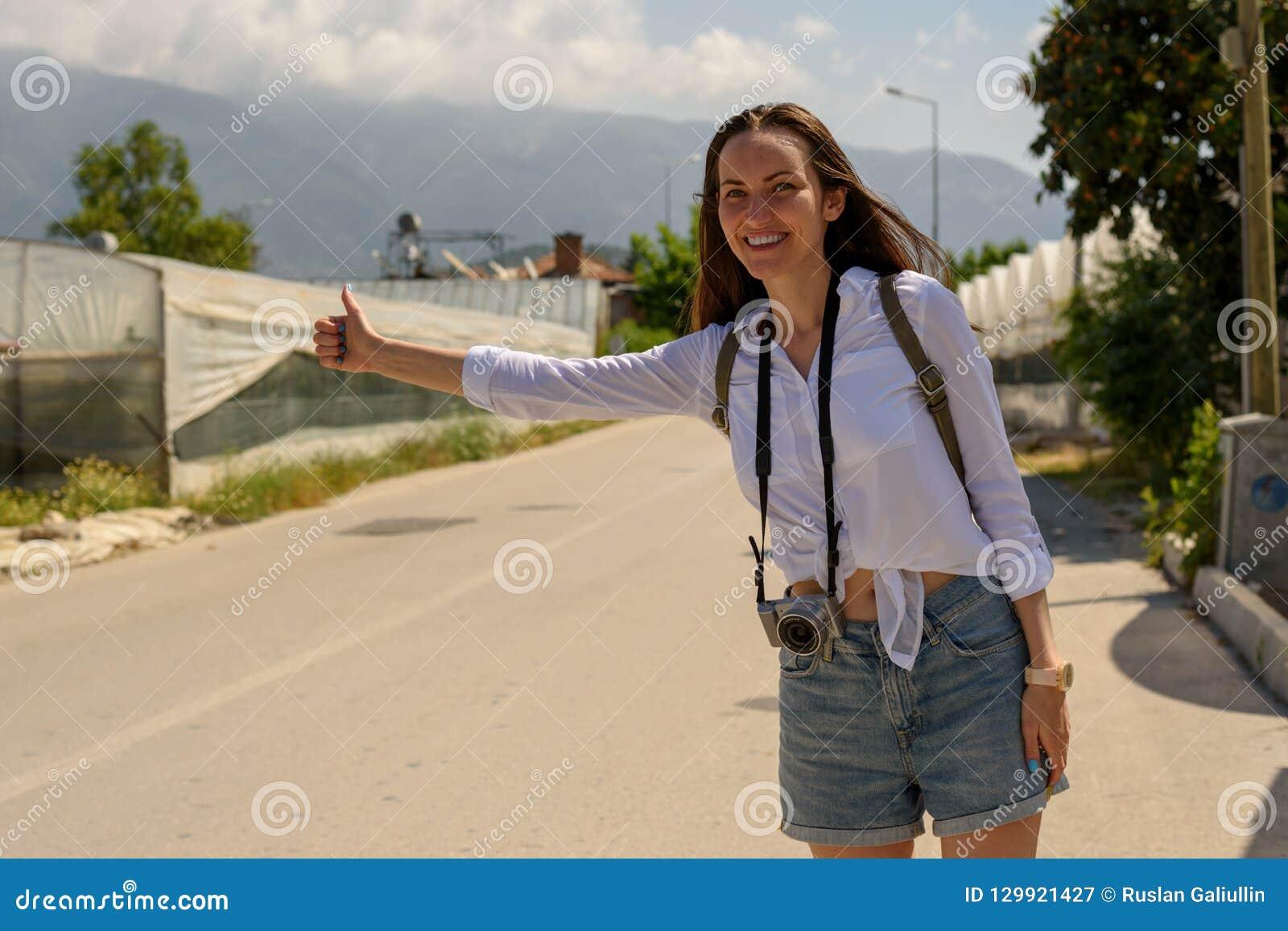 Μια γυναίκα στην πλευρά του δρόμου πιάνει ένα περνώντας αυτοκίνητο, να κάνει ωτοστόπ