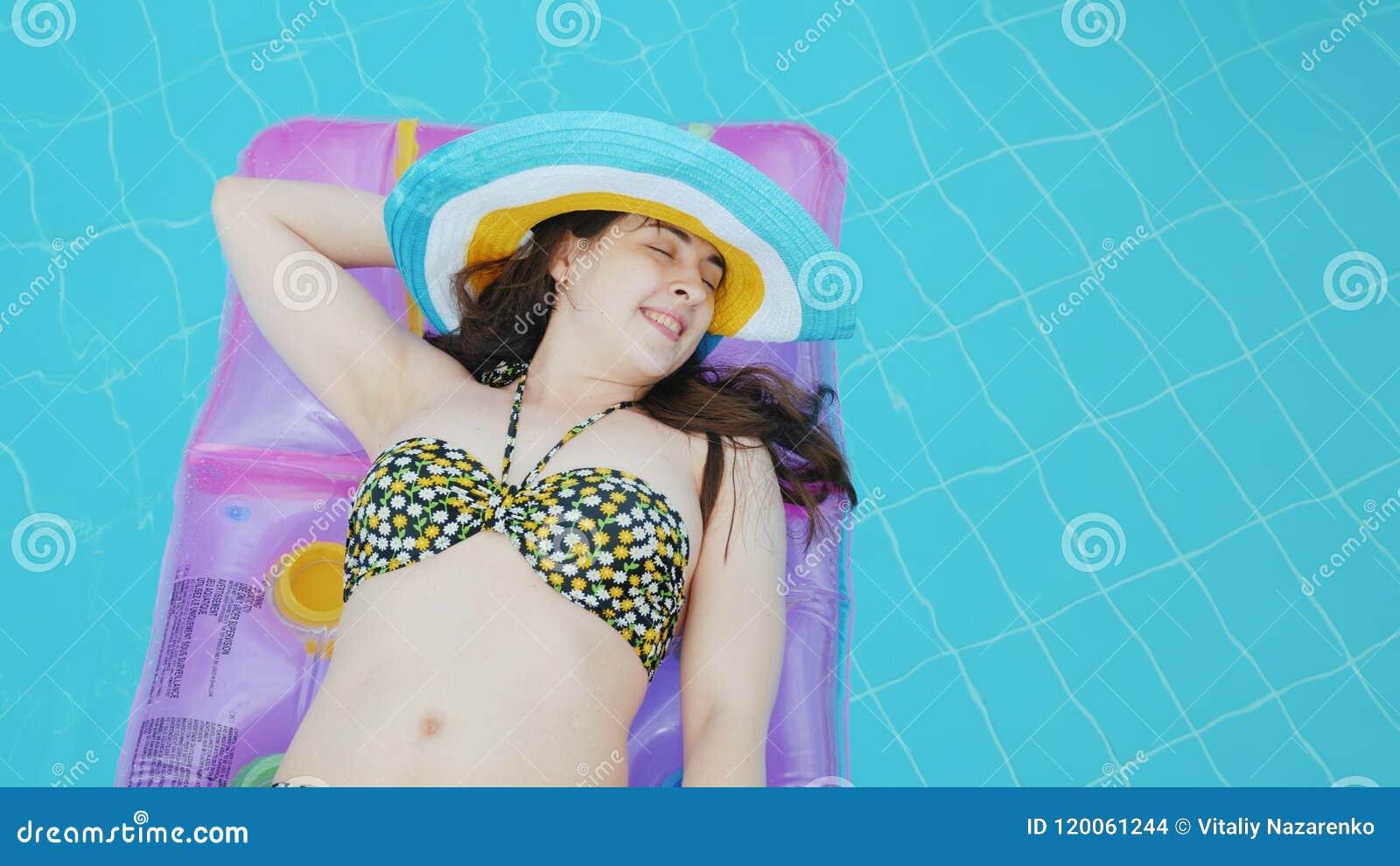 Μια ελκυστική νέα γυναίκα σε ένα καπέλο επιπλέει σε ένα διογκώσιμο στρώμα στη λίμνη ιδανική έννοια διακοπών