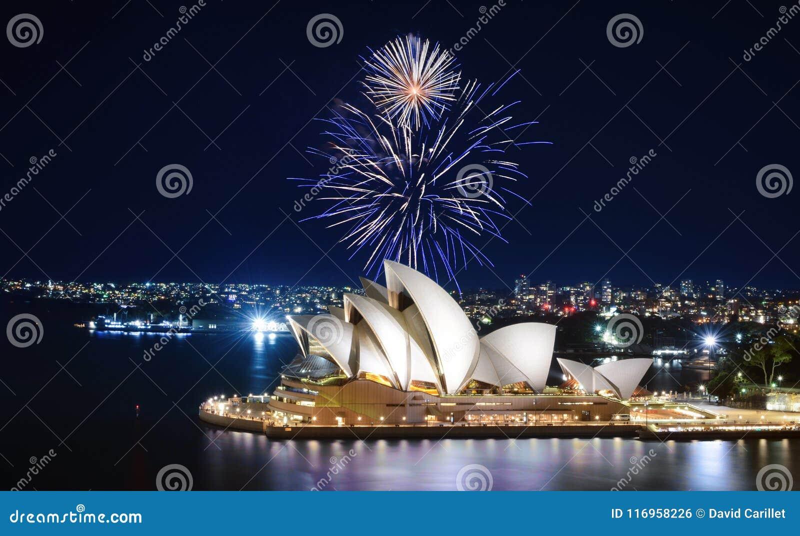 Μια εντυπωσιακή επίδειξη των πυροτεχνημάτων ανάβει επάνω τον ουρανό μπλε και άσπρος πέρα από τη Όπερα του Σίδνεϊ