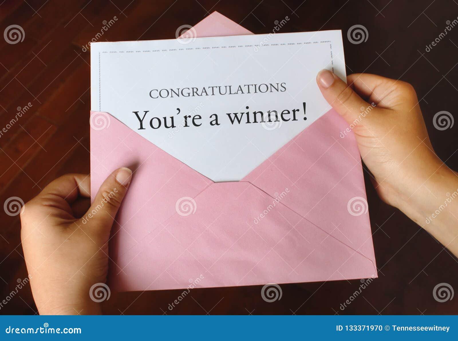 Μια επιστολή που λέει τα συγχαρητήρια που είστε νικητής! με τα χέρια που κρατούν έναν ρόδινο φάκελο
