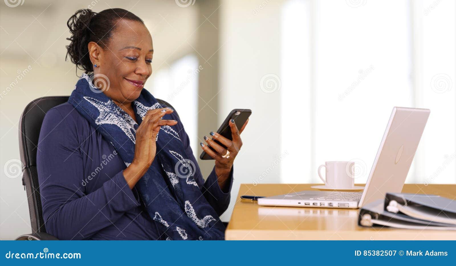 Μια επιχειρηματίας αφροαμερικάνων χρησιμοποιεί το κινητό τηλέφωνό της στο γραφείο της