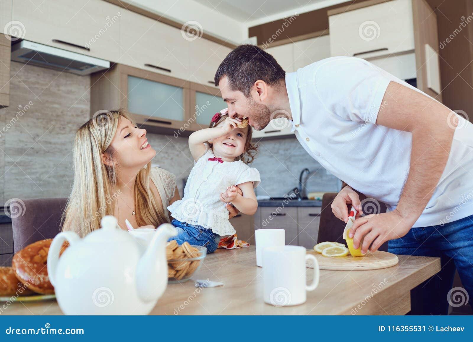 Μια ευτυχής οικογένεια τρώει στην κουζίνα