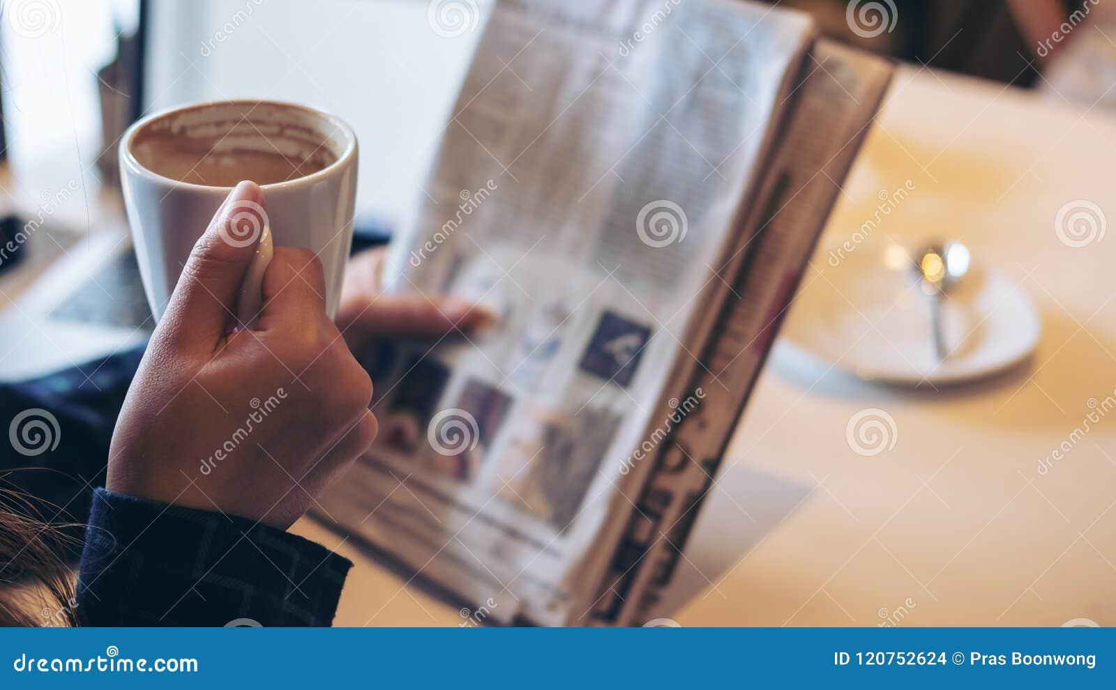 Μια εφημερίδα ανάγνωσης επιχειρησιακών γυναικών και ένας καφές κατανάλωσης