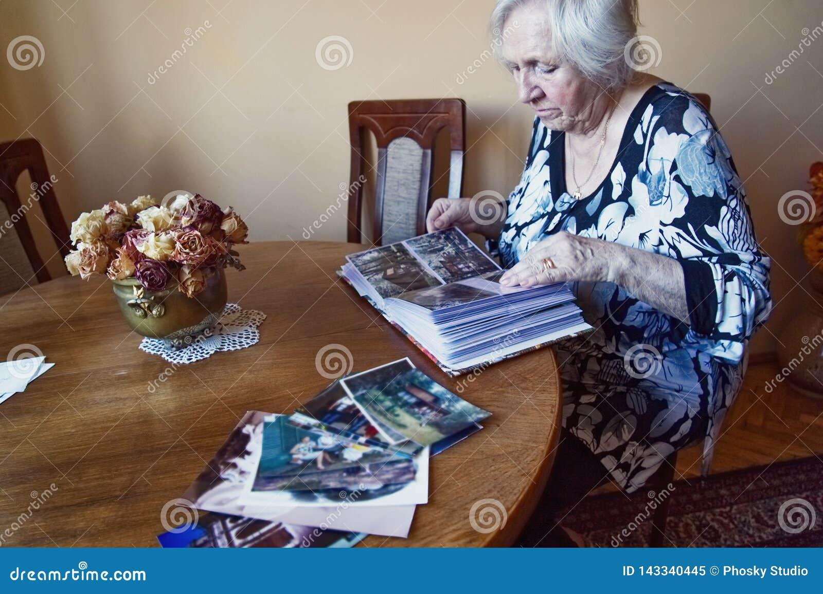 Μια ηλικιωμένη γυναίκα κοιτάζει μέσω ενός λευκώματος φωτογραφιών
