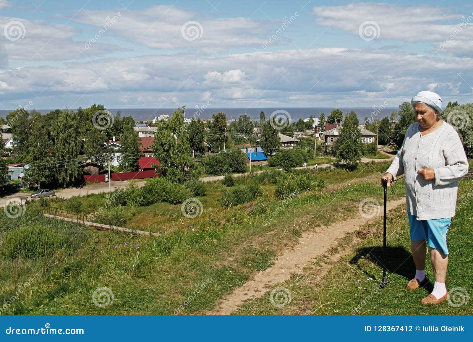 Μια ηλικιωμένη γυναίκα με έναν κάλαμο στέκεται στο υπόβαθρο του χωριού και τη λίμνη σε Belozersk