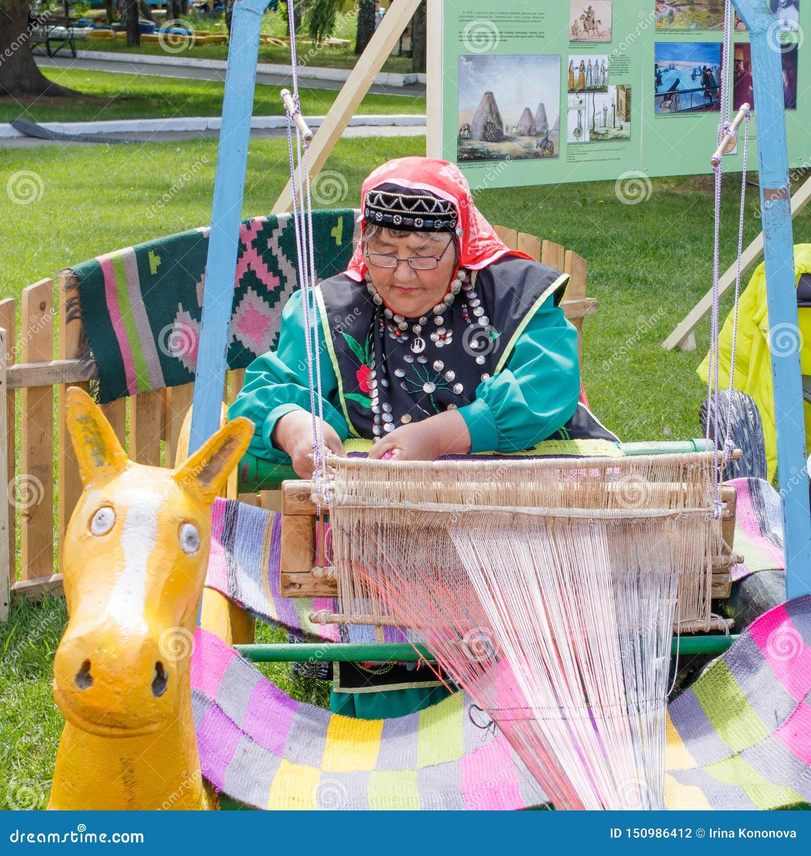 Μια ηλικιωμένη γυναίκα στα από το $λ* ψασχκηρ ενδύματα είναι καθισμένη σε έναν αργαλειό και υφαίνει έναν τάπητα Εθνική εορτή Saba
