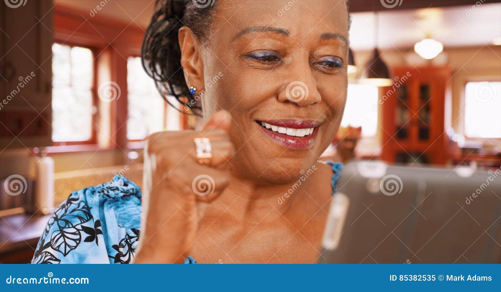 Μια ηλικιωμένη γυναίκα αφροαμερικάνων χρησιμοποιεί την ταμπλέτα της στην κουζίνα της