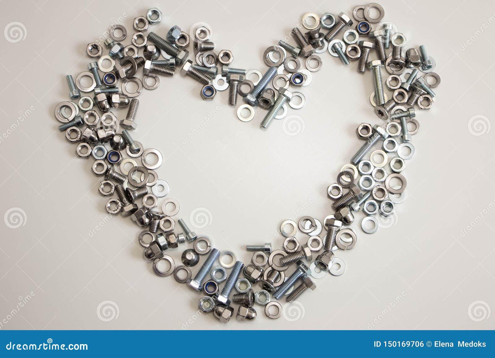 Μια καρδιά ευθυγράμμισε με ποικίλα καρύδια, μπουλόνια, βίδες και πλυντήρια με το κενό διάστημα μέσα σε ένα ανοικτό γκρι υπόβαθρο