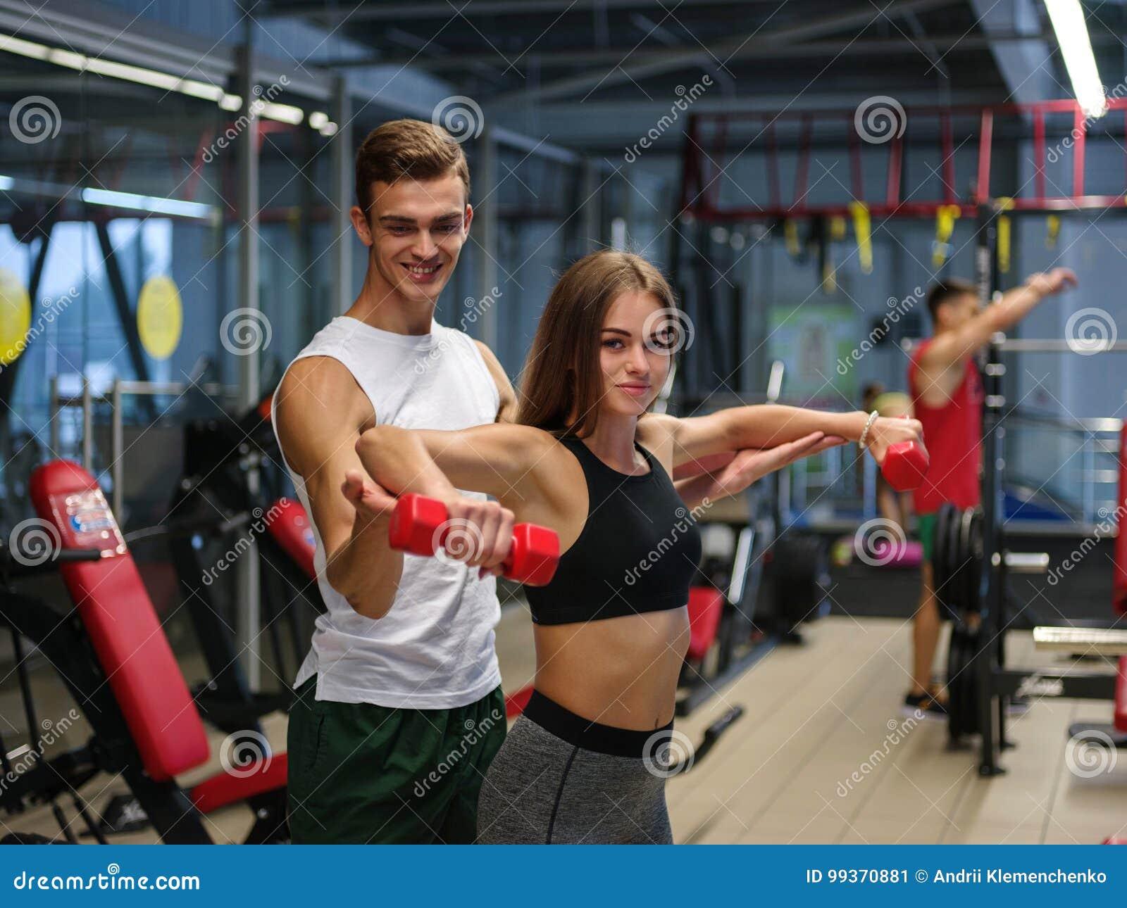 Μια κυρία που κάνει τις ασκήσεις με τους κόκκινους αλτήρες σε ένα υπόβαθρο γυμναστικής Ένας προσωπικός εκπαιδευτής που βοηθά έναν