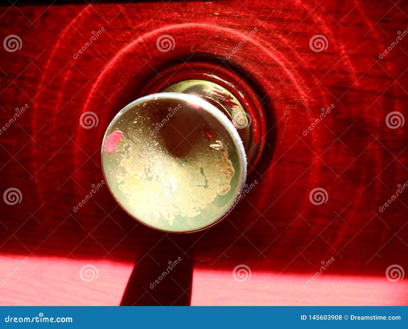 Μια λαμπυρίζοντας κόκκινη πόρτα με ένα τραγανό χρυσό εξόγκωμα