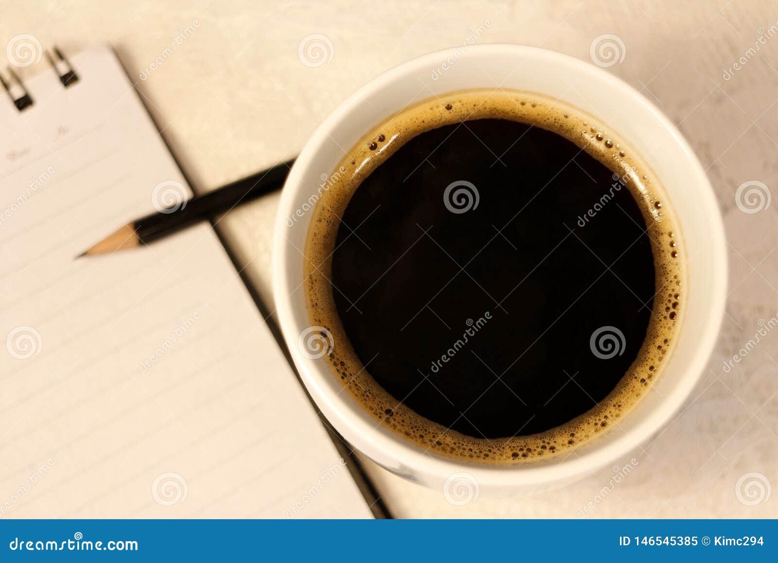 Μια μαύρη καυτή σπόλα του καφέ στέκεται δίπλα σε ένα σημειωματάριο με μια μάνδρα