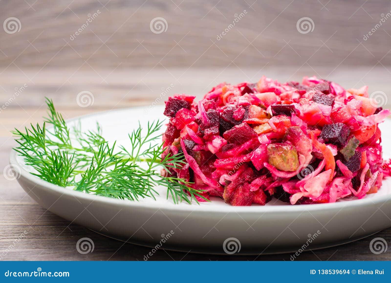 Μια μερίδα του vinaigrette - μια σαλάτα των βρασμένων λαχανικών, sauerkraut και των παστωμένων αγγουριών σε ένα πιάτο σε έναν ξύλ