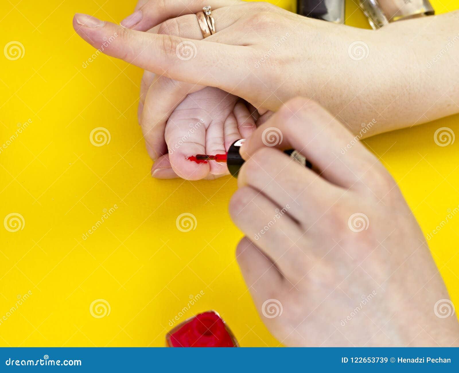 Μια μητέρα χρωματίζει toenails της με την λίγη κόρη, ένα κίτρινο υπόβαθρο, καλλυντικά κινηματογραφήσεων σε πρώτο πλάνο